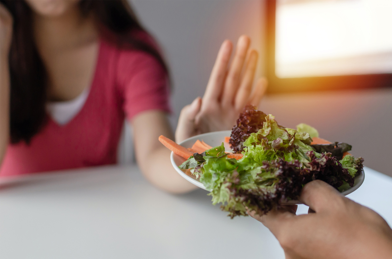 a women refusing to eat a plate of small veggies